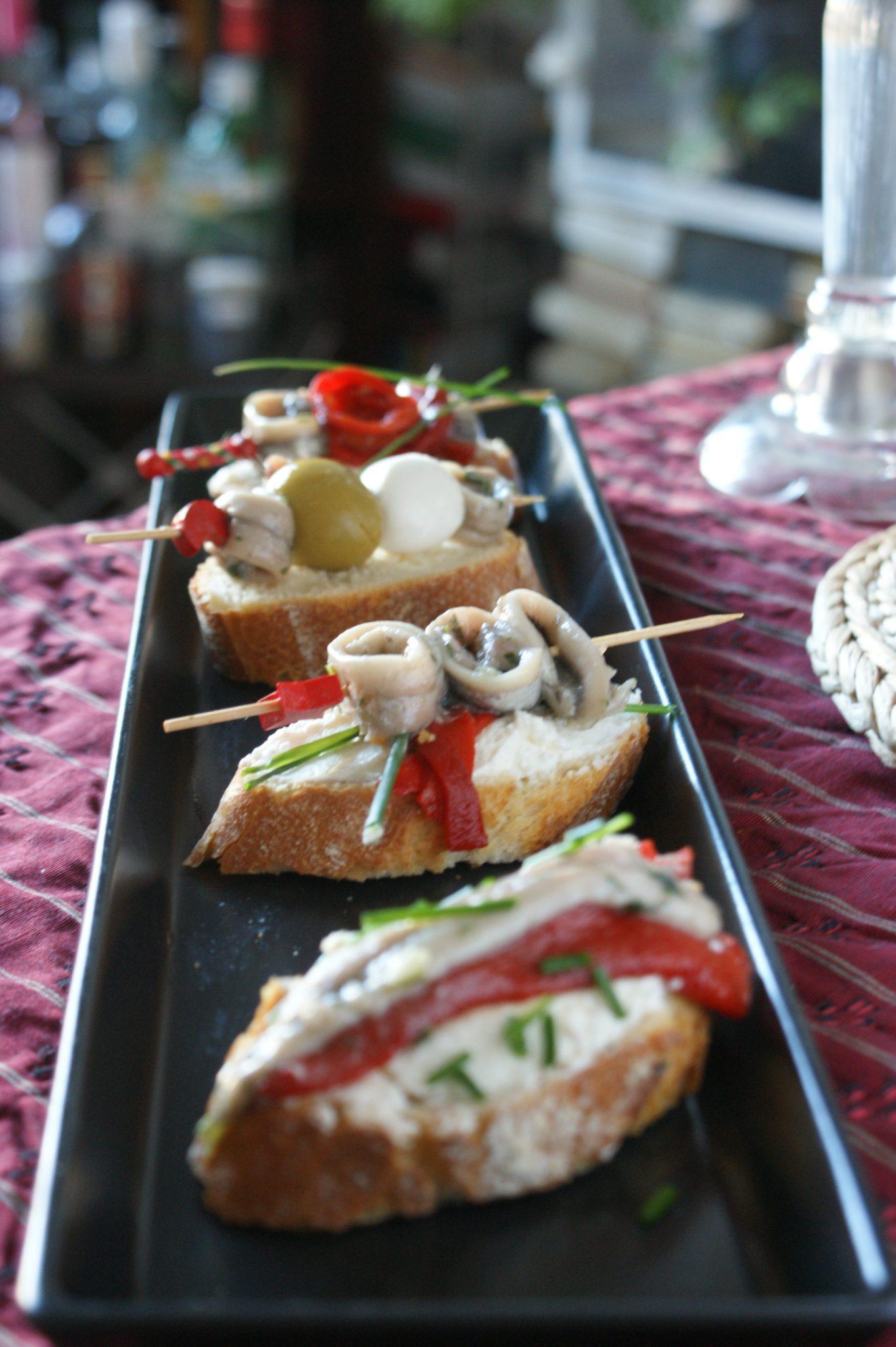 Boquerones en vinagre con pimientos sobre mousse  de queso y mantequilla de anchoas